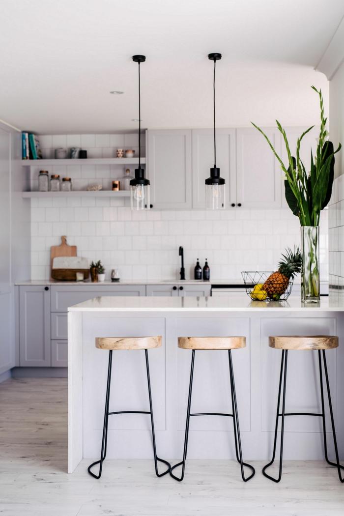 kleine moderne Küche mit Kochinsel, monochrome Einrichtung in weiß, zwei schlichte Hängelampen, Vase mit grünen Pflanzen