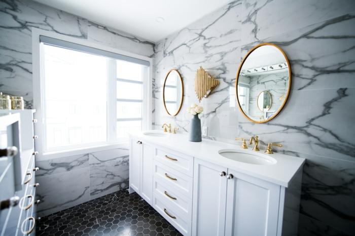 Zwei runde Spiegel mit goldenen Rahmen, weiße Schränke, Wände mit Marmor-Effekt, Badspiegel nach Maß, schwarze Bodenfliesen