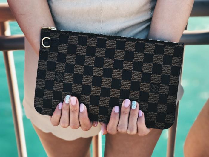 elegante maniküre mit bunten farben diy künstliche nägel entfernen zuhause hände halten kleine tasche