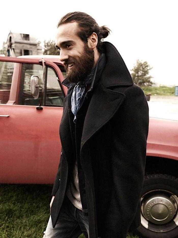 roter Pickup im Hintergrund, modisch gekleideter Mann im schwarzen Mantel, braune Haare im Dutt und Bart, Frisuren Männer mittellang