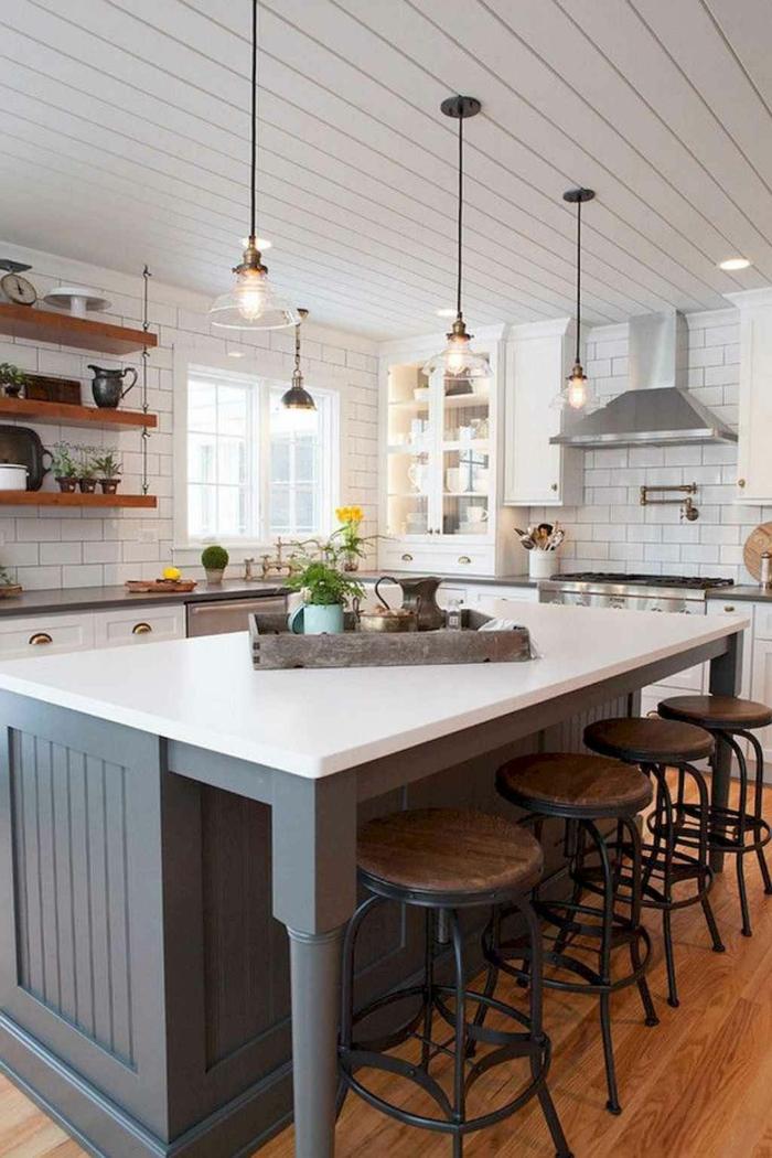 Moderne Küchen mit Insel, in blaue mit weißer There, vier Hängelampen, weiße Fliesen wie Backsteine, offene Regale aus Holz