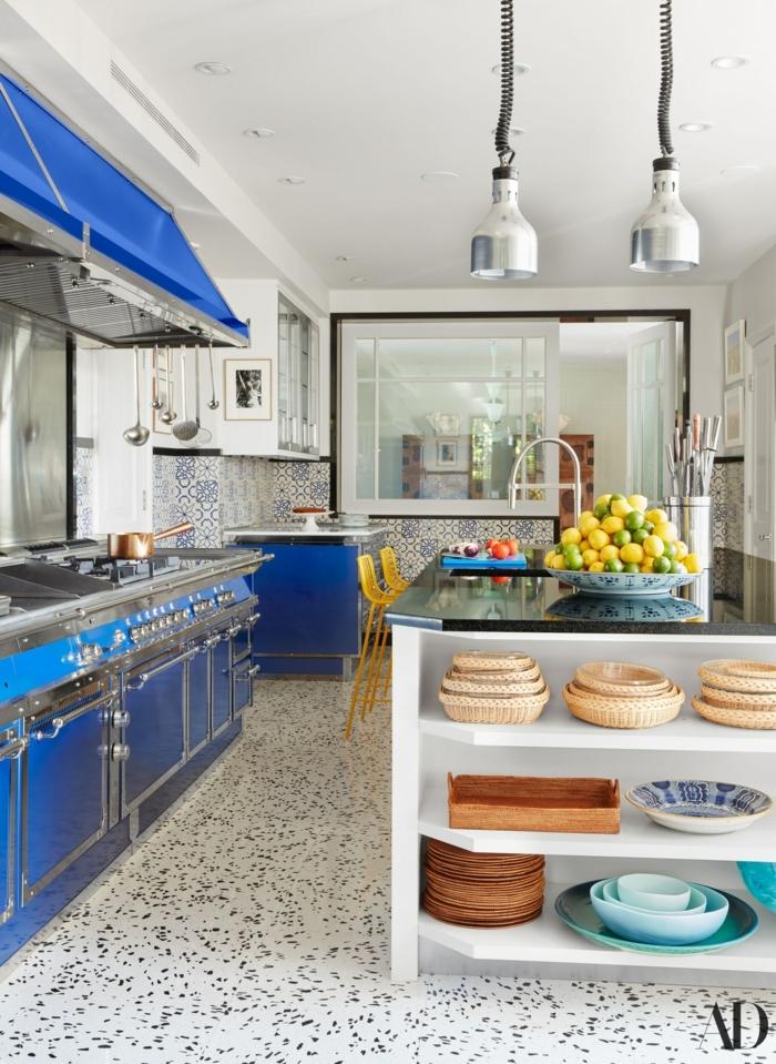 Kochinsel mit Theke, grell blaue Küche und gelbe Stühle, Teller voll mit Zitronen und Limetten, portugiesische Fliesen