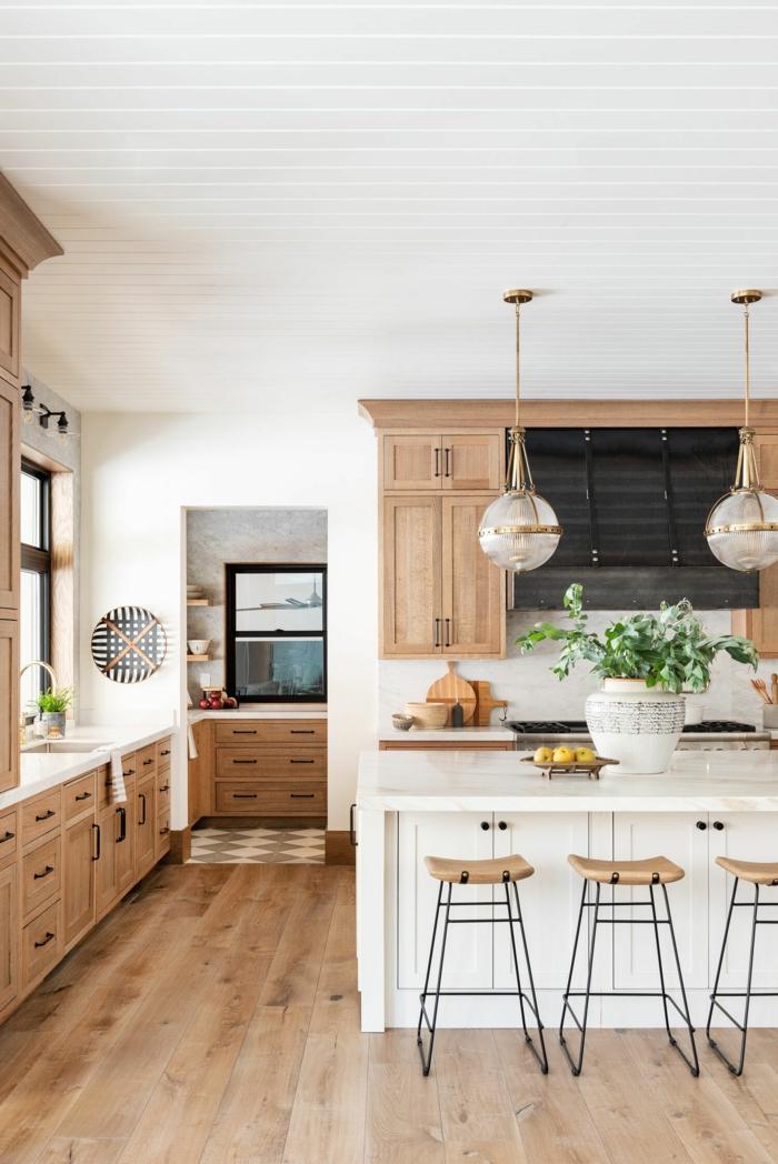 weiße Kochinsel mit Theke und Schränke, hölzerne Küchenschränke. große Küche mit Fenster, zwei Hängelampen,