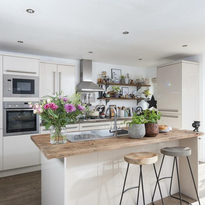 Inspiration für die Gestaltung einer kleinen Küche mit Kochinsel, weiße Kücheninsel mit hölzerne Theke, Blumen als Dekoration