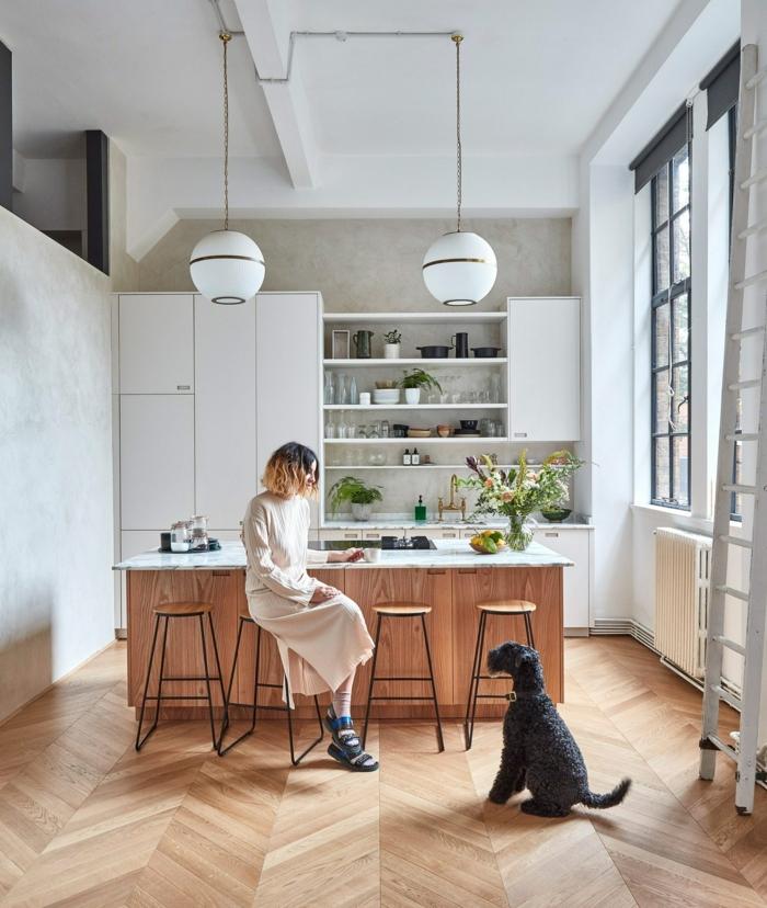 elegante Frau sitzt auf einem Stuhl in ihrer Küche, schwarzer Hund, Kücheninsel mit Sitzgelegenheit, großes französisches Fenster