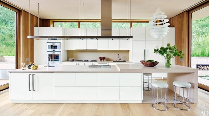 Kochinsel mit integriertem Esstisch, Interior Design von großer Küche in weiße Farbe, Wände in Holztöne, französische Fenster