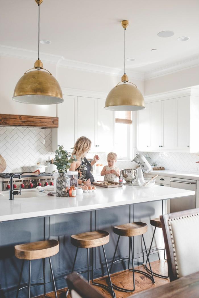 Mutter und kleines Kind kochen zusammen, blaue Kochinsel mit Theke in weiß, zwei goldene Hängelampen, Küchenschränke weiß