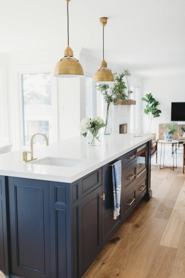 moderne Küchen mit Insel in dunkelblauer Farbe und weiße Theke, zwei Hängelampen in goldenen Farbe, grüne Pflanzen Dekoration