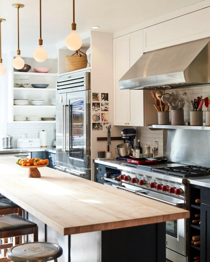 Moderne Küche mit Kochinsel, Theke aus Holz, Metall Ofen, Schränke mit Schüsseln und Tellern, schlichte Lampen