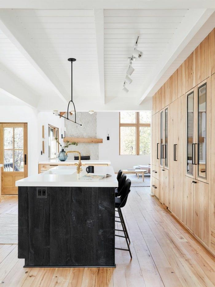 Moderne Küchen mit Insel in schwarz, hölzerne Küchenschränke und Boden, Waschbecken mit goldene Mischbatterie