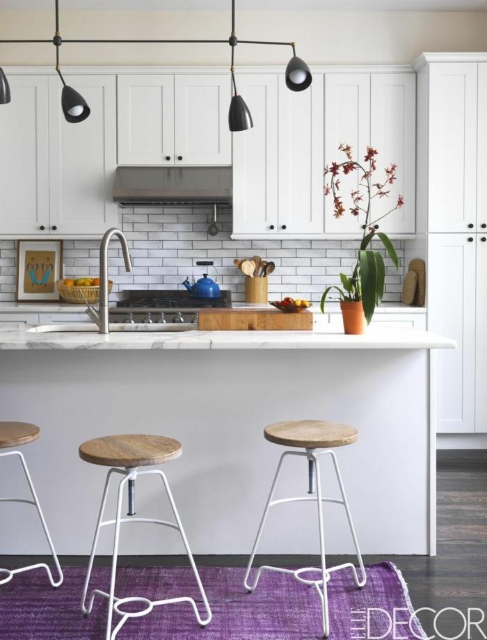 Kücheninsel Ikea mit Waschbecken, schwarze Lampen, Dekoration mit lila Teppich und schöner Blume, weiße Fliesen,