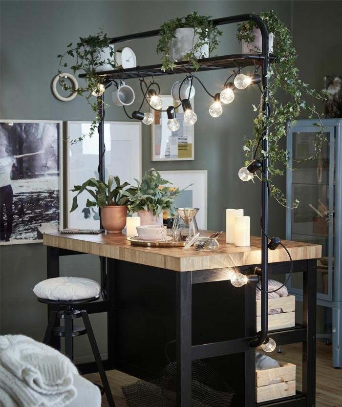 Kücheninsel Ikea in schwarz mit Holztheke, Insel dekoriert mit Lampen und grünen Schlingpflanzen, Wand in grün,