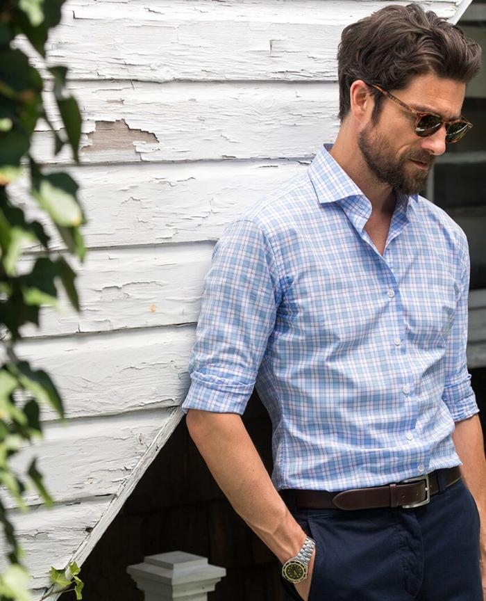 Trend Frisuren 2020, Mann im eleganten Outfit, blaues Hemd und blaue Hose, kurze braune Haare und Bart
