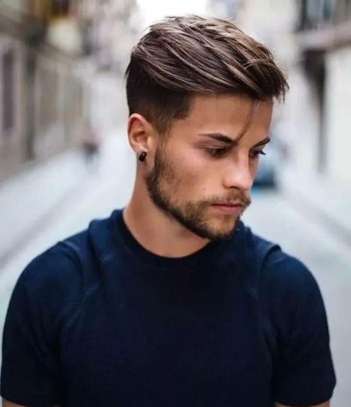 Street Style Fotografie, Bild von einem jungen Mann im schwarzen Sweatshirt, dunkelblonde Haare und kurzer Bart, Undercut Frisuren Männer