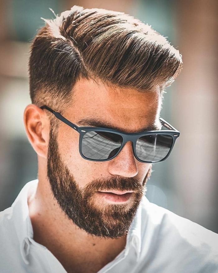 Männer Frisuren kurz 2020, Herr mit braunen Haaren und kurzer Bart, angezogen im weißen Hemd, schwarze Sonnenbrillen