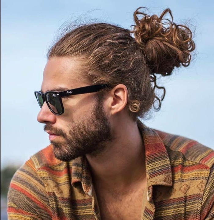 Mann mit dunkelblonden Haaren im Dutt angezogen im bunten Hemd, Haarschnitt lange Haare, kurzer Bart