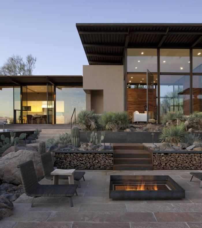 luxuriöses design haus gartengestaltung ideen mit steinen und feuerstelle zwei liegestühle