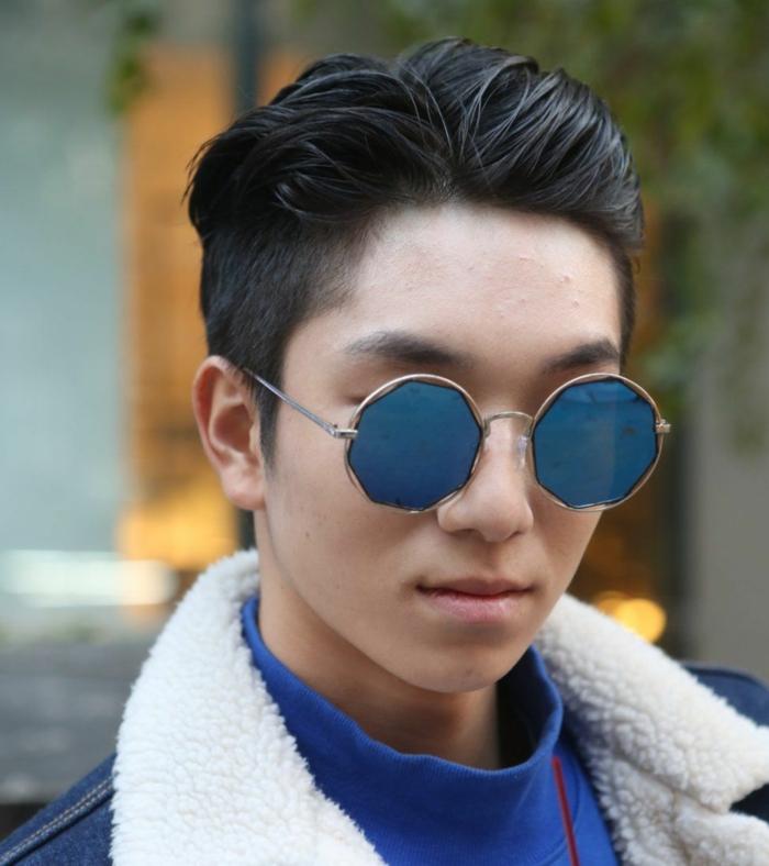 coole runde blaue Sonnenbrillen, junger Mann mit schwarzen Haaren, Trend Frisuren 2020 für Männer, Jeansjacke mit weißem Kragen