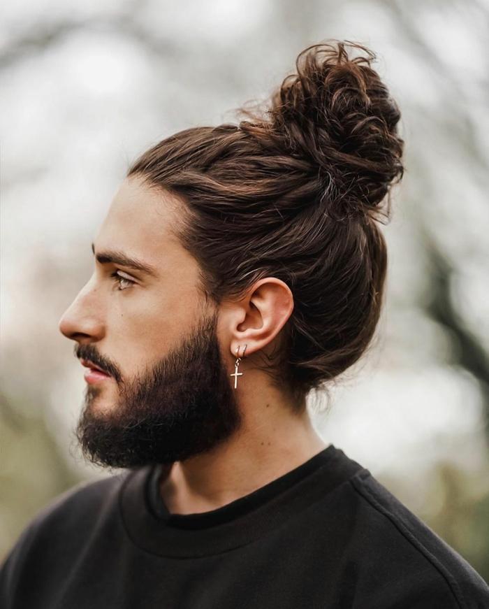 Mittellange Haare Frisur 2020, dunkelbraune Haare im messy Dutt, schwarze Bluse, Ohrring mit einem Kreuz,