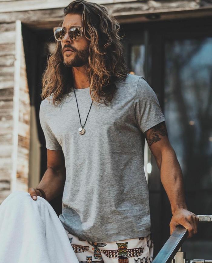 Haarschnitt lange Haare, Männerfrisuren 2020, lässig angezogener Mann in grauem T-Shirt und bunten Hosen
