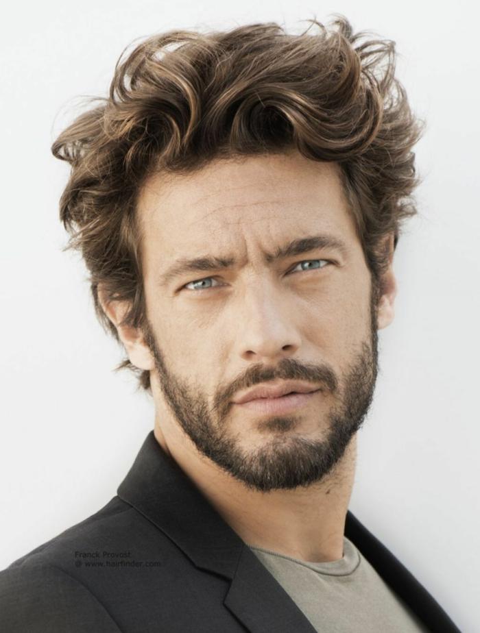 längere Frisurentrends 2020 für Männer, dunkelblonde Haare, Mann mit blauen Augen, kurzer Bart, schwarze Jacke