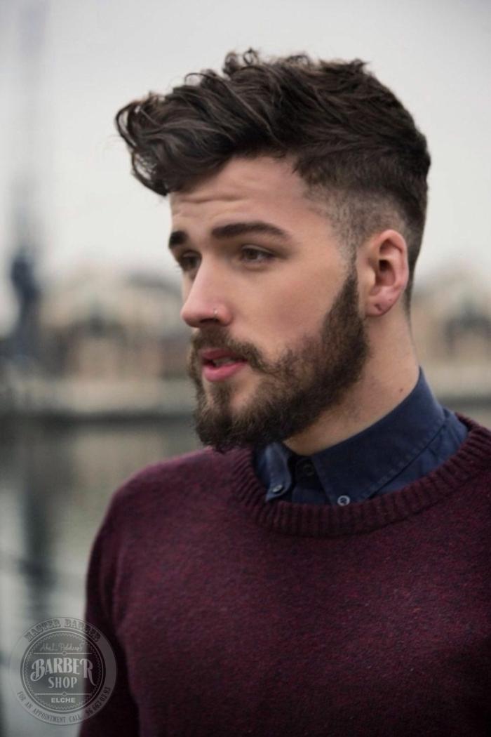 Мännerfrisuren 2020 kurz mit Undercut, burgundroter Pullover und blaues Hemd, mittellanger Bart, braune Haare