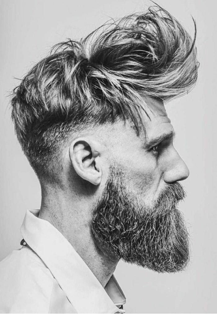 Undercut Frisuren Männer, dicker Bart, blonde Haare, Mann angezogen im weißen Hemd, schwarz weißes Foto