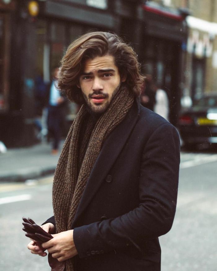 Männerfrisuren mittellang, elegantes Styling im schwarzen Mantel und braunem Schal, street style Inspiration, Mann hält Handschuhe in der Hand
