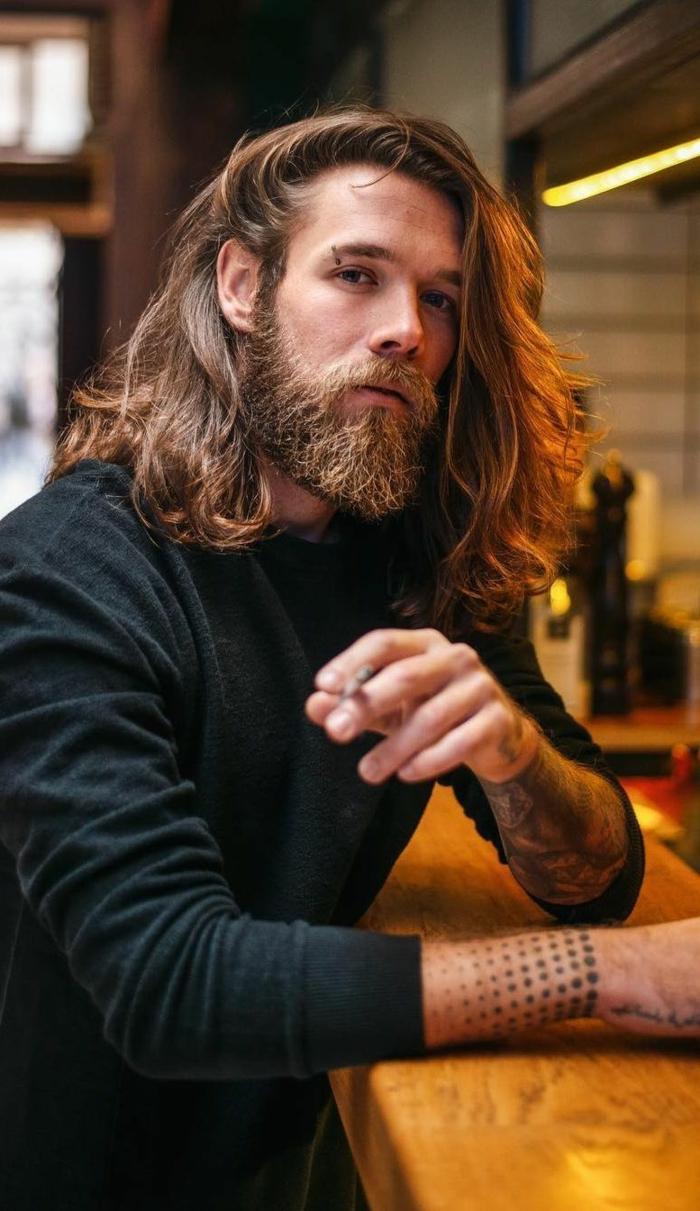 Mittellange Haare Frisur mit buschigem Bart, Tattoos auf den Armen, Mann angezogen in schwarze Bluse, dunkelblonde Haare