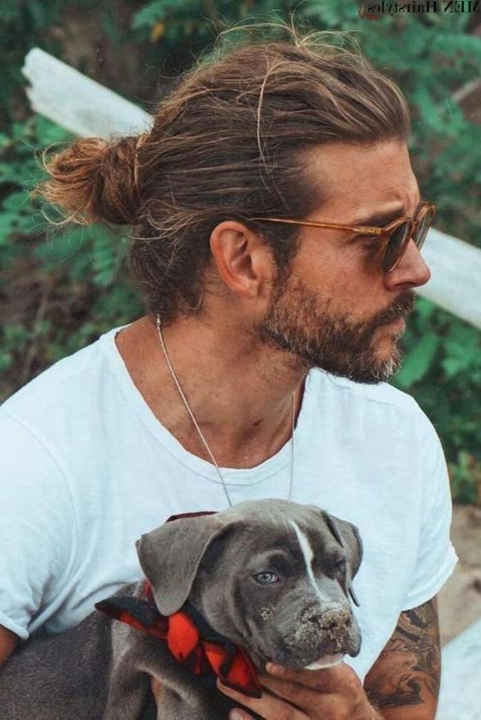 Haarschnitt lange Haare 2020, Mann mit dunkelblonden Haare im Man Bun, Herr trägt ein weißes T-Shirt, hält einen kleinen dunkelgrauen Hund
