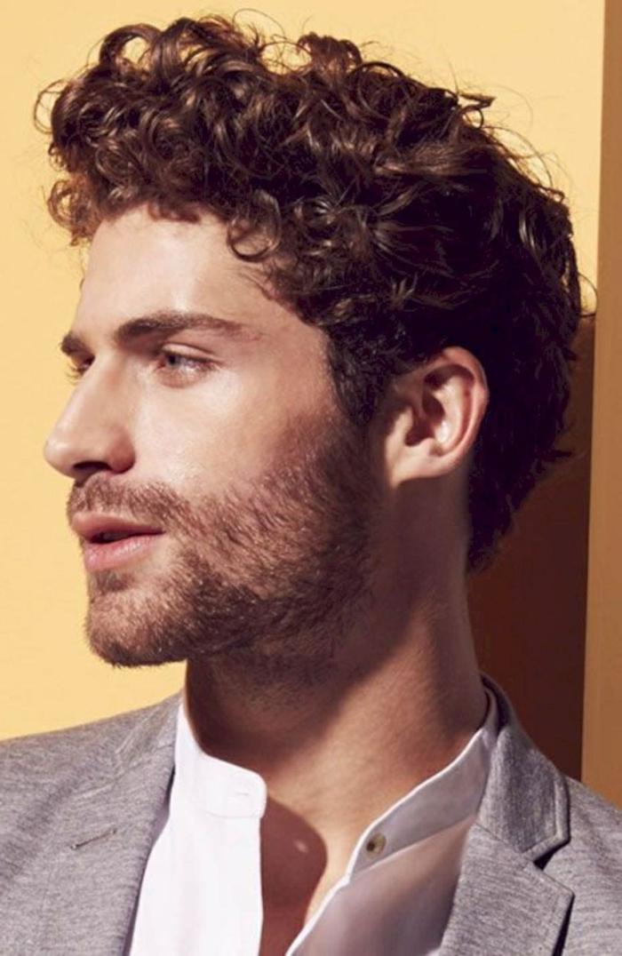 junger Mann mit lockigen braunen Haaren, lässig gekleidet im grauen Jackett und weißes Hemd, moderne Kurzhaarfrisuren