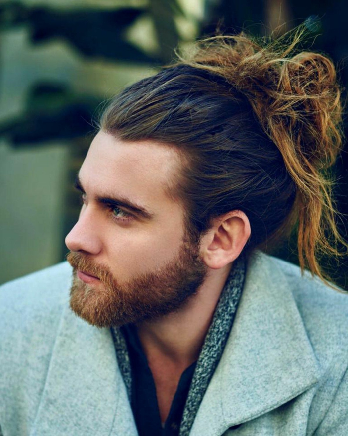Mann mit lange im messy Dutt hochgesteckten Haaren, angezogen im grauen Mantel, Haarschnitt lange Haare