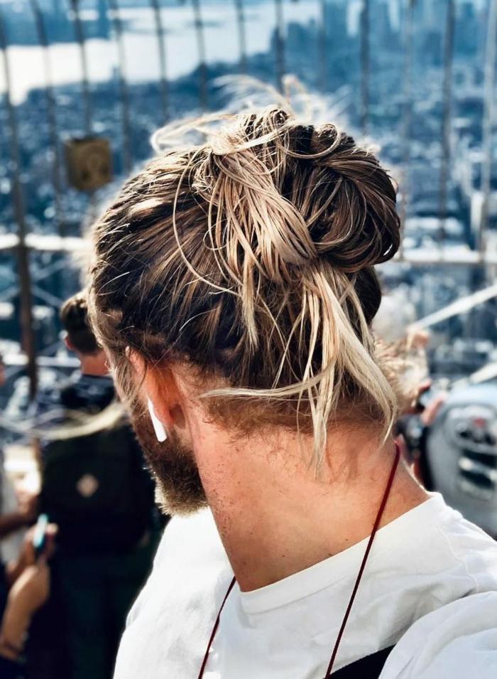 Mann mit hochgesteckten im Dutt langen Haaren mit blonden Strähnen, Frisurentrends 2020 für Männerfrisuren