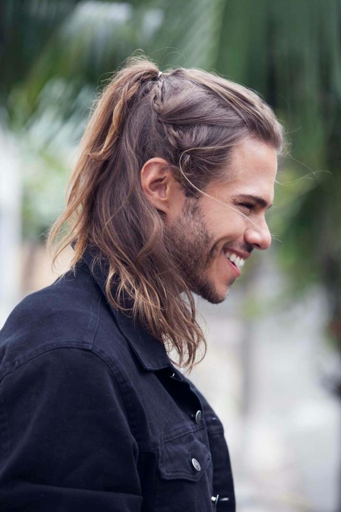 Männerfrisuren mittellang, Halb hoch halb unten mit geflochtenem Zopf, schwarze Jeansjacke, kurzer Bart