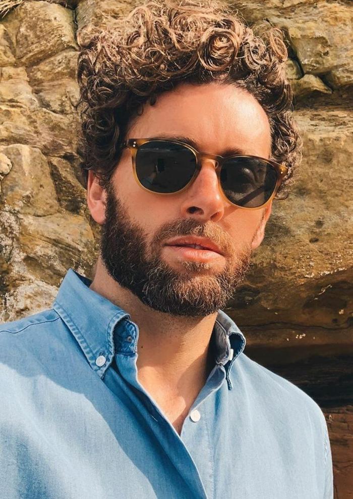 Männer Frisuren kurz, Mann mit braunen lockigen Haaren und kurzem Bart, Casual Outfit, blaues Hemd und schwarze Sonnenbrillen