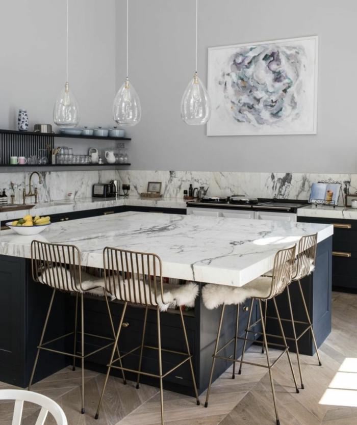 Kücheninsel mit Sitzgelegenheit, weiße Theke aus Marmor, blaue Schränke für die Küche, abstraktes Gemälde an die Wand