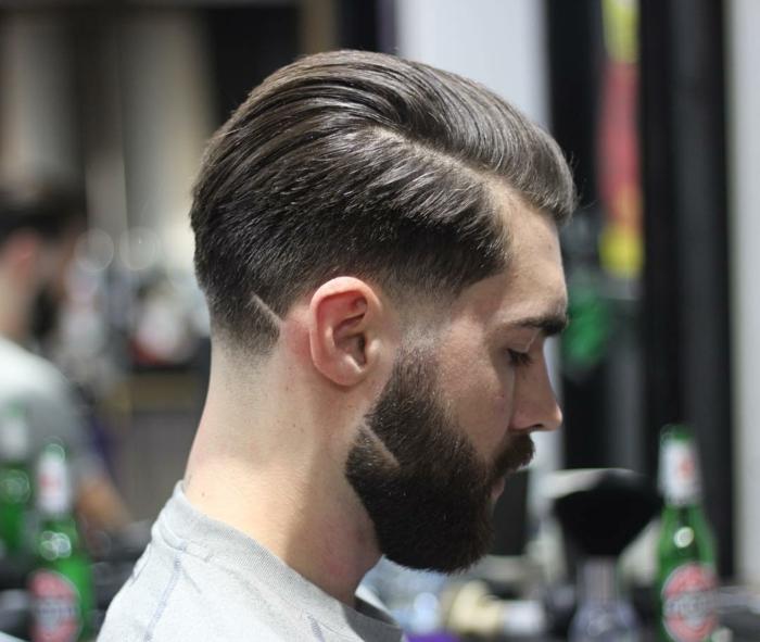 Foto von einem jungen Mann mit modischem Haarschnitt, Männer Frisuren kurz 2020, braune Haare und buschiger Bart