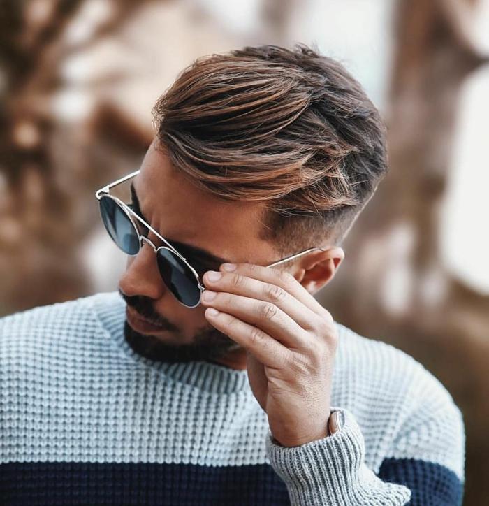 Männer Kurzhaarschnitt mit Undercut, Mann trägt runde Sonnenbrillen und einen grauen Pullover, dunkelbraune Haare