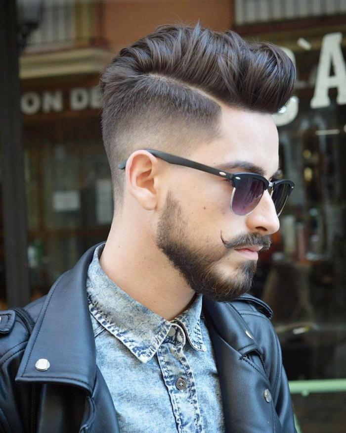 moderne Kurze Männerfrisuren, dunkelbraune Haare und kurzer Bart, Mann angezogen im blauen Hemd und schwarze Lederjacke
