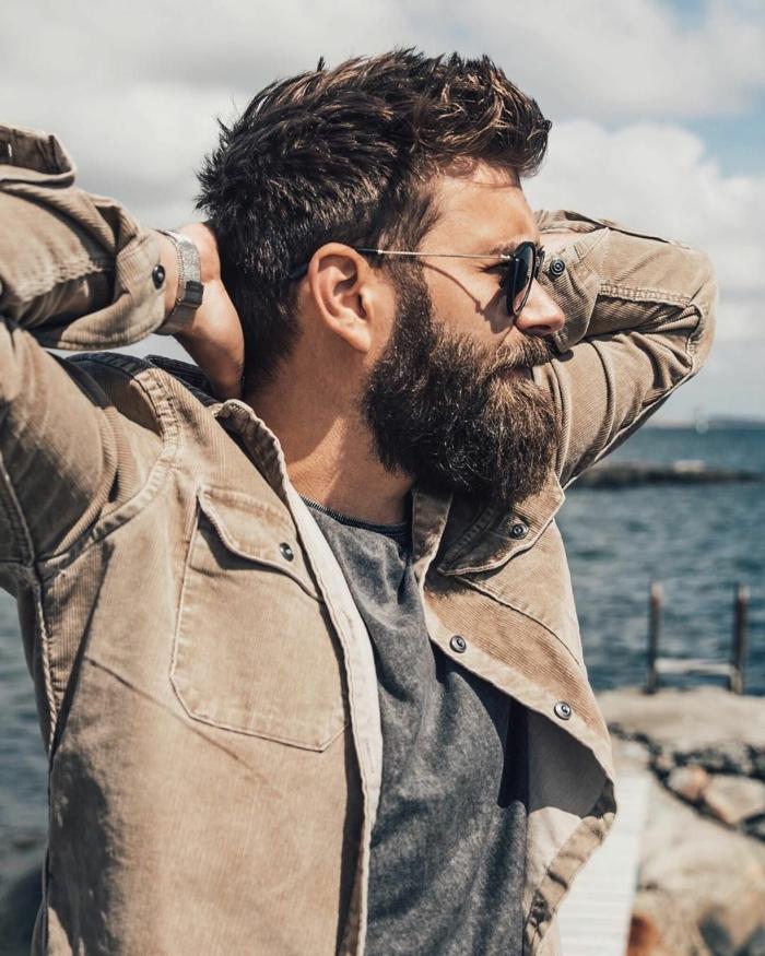 Männer Frisuren 2020, Mann mit kurzen Haare und buschigem Bart, Outfit mit beigem Hemd und graues T-Shirt