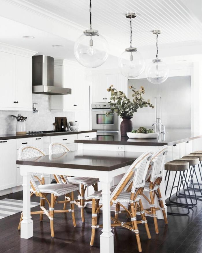 Kochinsel mit integriertem Esstisch, Stühle in verschiedene Stile, minimalistische Einrichtung in weiße und schwarze Farben,
