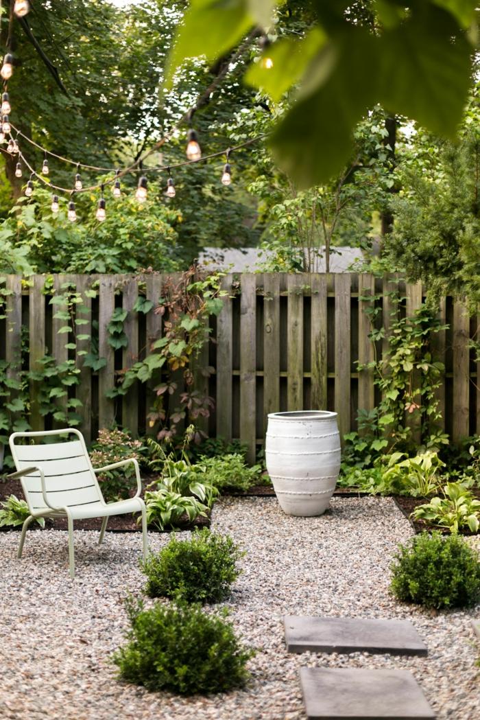 romantische gartengestaltung viele grüne pflanzen und bäume weißer stuhl kleine hängeleuchte sichtschutz garten steinbeet anlegen