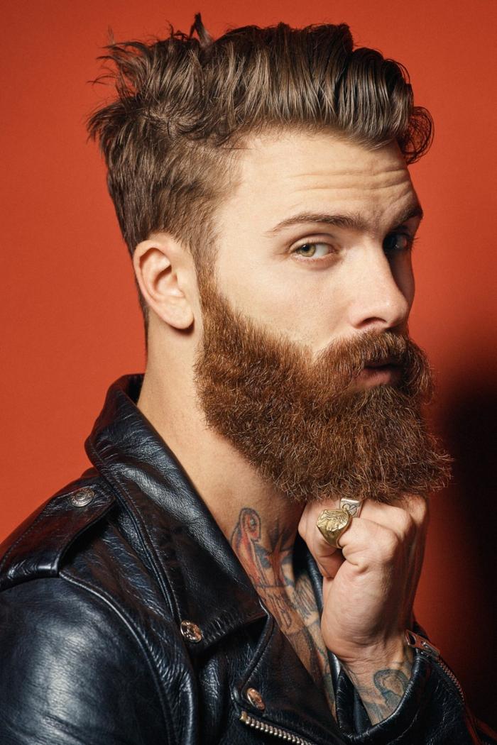 Mann mit roten Haaren und langem Bart, angezogen in schwarze Lederjacke, Männer Frisuren kurz 2020, bunte Tattoos