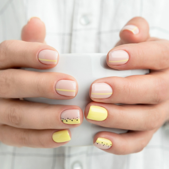 schöne bunte schlichte gelnägel in beige und gelb gel nagellack entfernen zuhause hand hält eine tasse
