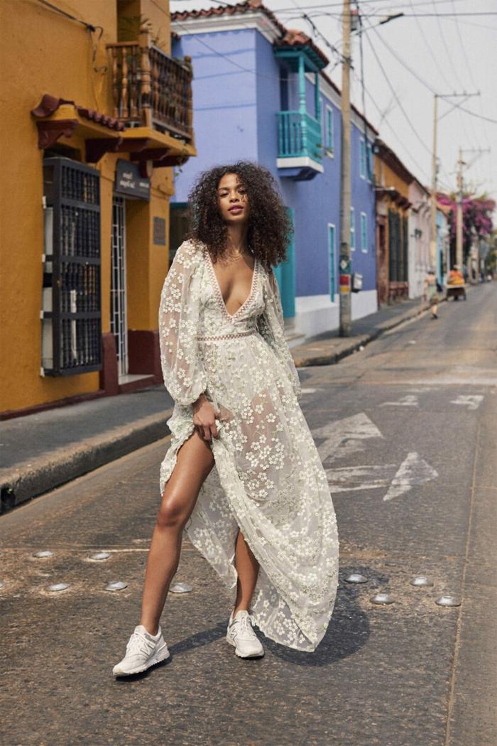 schöner street style sportlich chic weiße chunky sneackers sommerkleider lang elegant mit spitze frau mit lockigen haaren