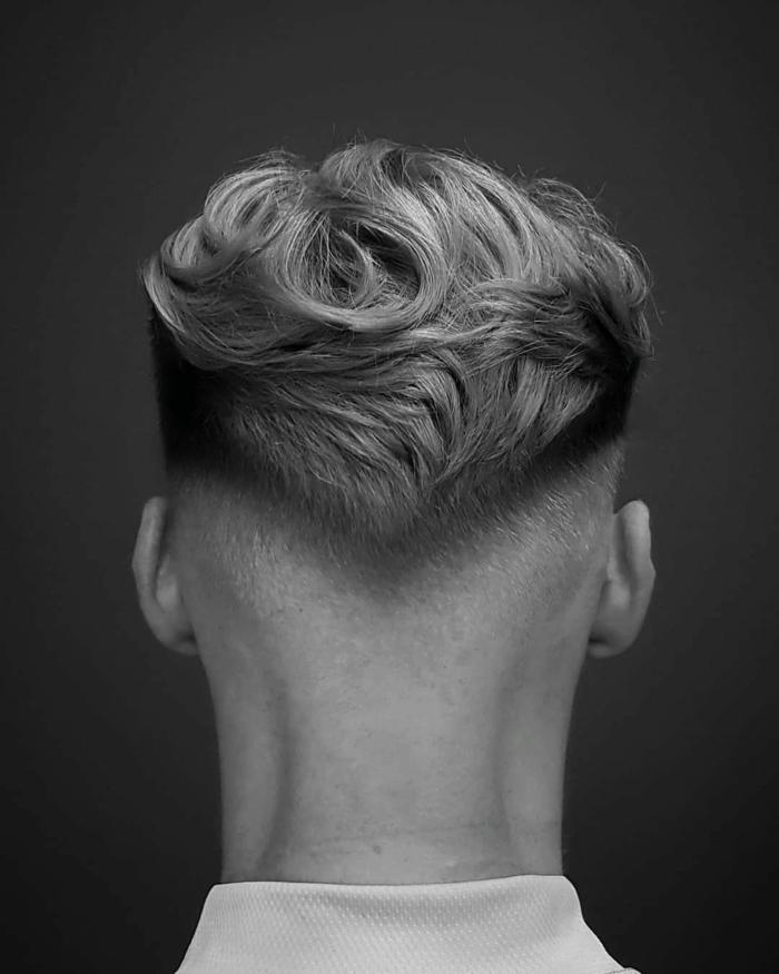 Frisurentrends 2020, Mann mit blonden leicht gewellten Haaren und Undercut Haarschnitt, schwarz weißes Foto,