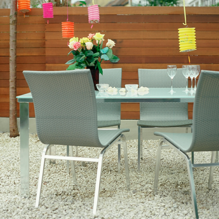 sichtschutz garten ideen holz moderne gartenmöbel vase mit schönen blumen bunte hängende laternen gartengestaltung mit steinen