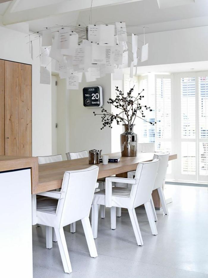 Kücheninsel mit Sitzgelegenheit, Holztisch mit weißen Stühlen, interessante Dekoration, große Vase aus Metall mit Blumen