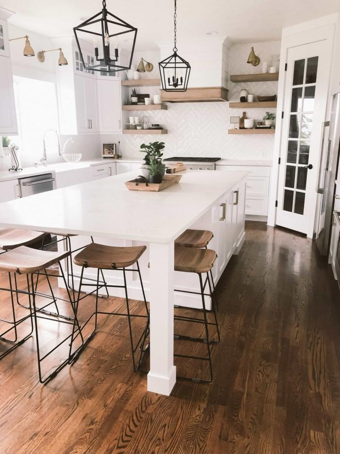 große Eckküche mit kleinem Fenster, Kücheninsel mit Sitzgelegenheit, Inneneinrichtung im skandinavischen Stil, Kombination aus Metall und Holz