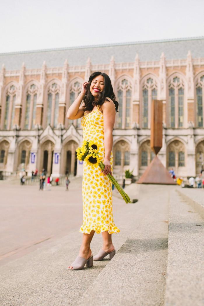 sommer kleidung damen langes gelbes kleid mit blumen sonnenblumenstrauß dame mit dunklen haaren
